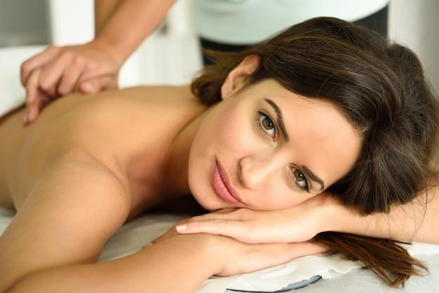 Jeune femme recevant un massage du dos relaxant dans un centre de spa.