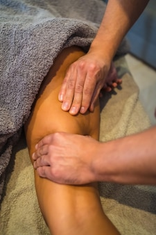 Une jeune femme recevant un massage des jambes d'un physiothérapeute. physio, ostéopathie