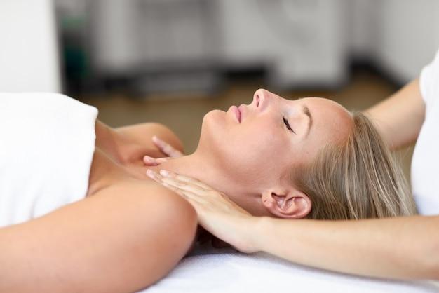Jeune femme recevant un massage de tête dans un centre de spa.