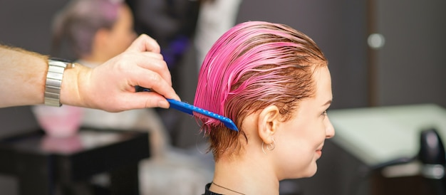 Jeune femme recevant un traitement capillaire après coloration rose à la main du coiffeur masculin dans un salon de coiffure