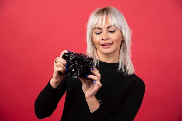 Jeune femme à la recherche d'un appareil photo sur fond rouge. photo de haute qualité