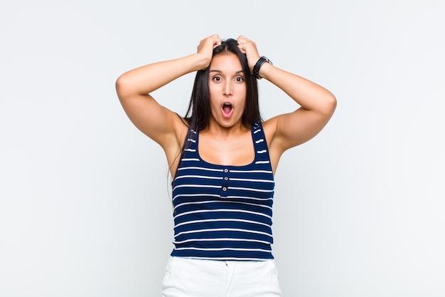 Jeune femme à la recherche excitée et surprise, bouche bée avec les deux mains sur la tête, se sentant comme un heureux gagnant