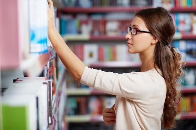 Jeune femme à la recherche d'un livre