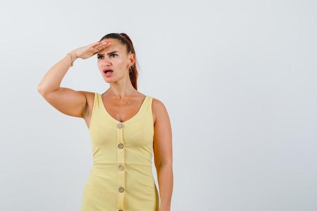 Jeune femme à la recherche de loin avec la main sur la tête en robe jaune et à la frustration. vue de face.
