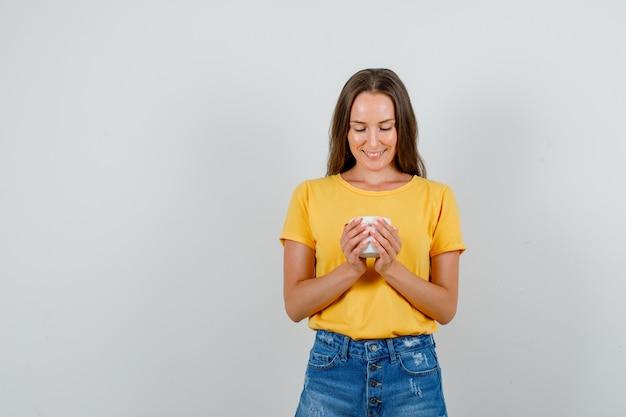 Jeune femme à la recherche en porte-crayon et souriant en t-shirt, short