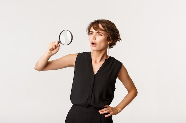 Jeune femme à la recherche de quelque chose, regardant à travers la loupe