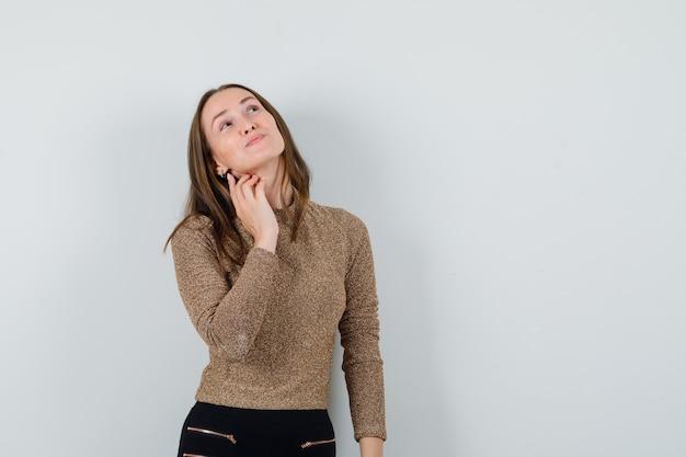 Jeune femme à la recherche de suite en chemisier doré et à l'optimiste