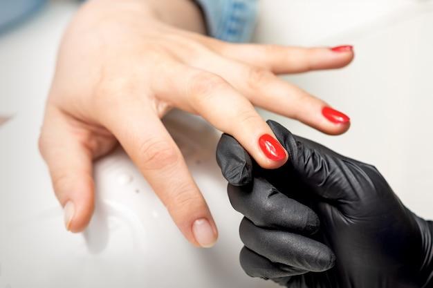 Jeune femme reçoit du vernis à ongles rouge par un maître de manucure professionnel dans un salon de manucure