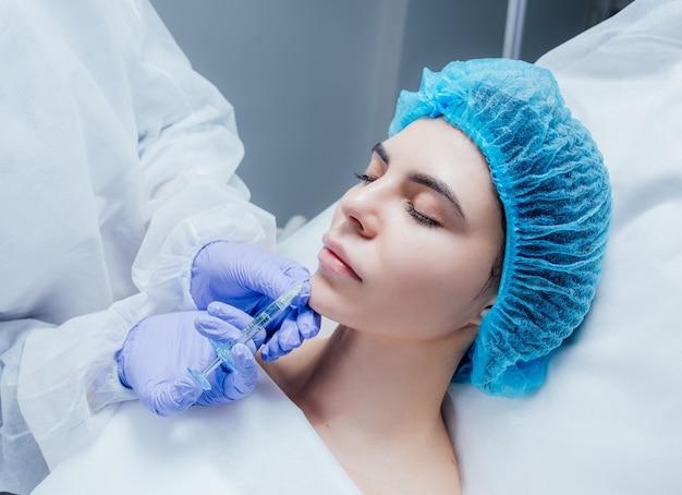 Une jeune femme reçoit une injection de botox dans ses lèvres. femme, dans, salon beauté