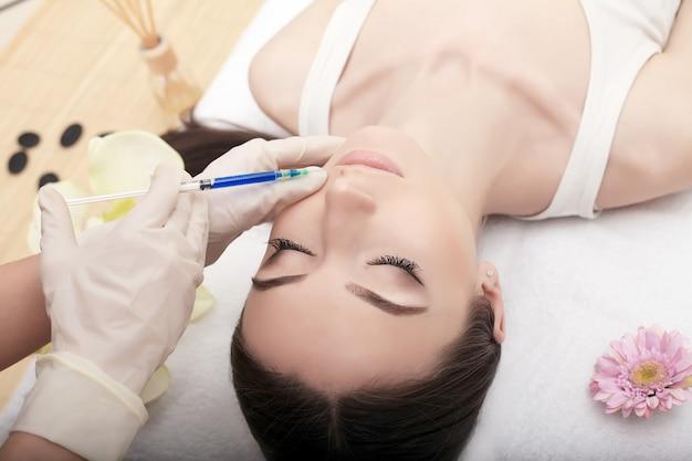 Jeune femme reçoit une injection dans son front