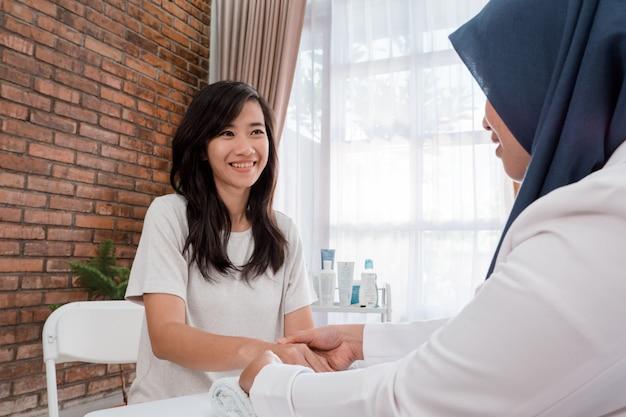 Jeune femme reçoit une lotion pour les mains avec une esthéticienne