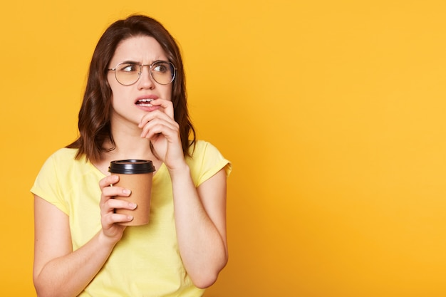 Jeune femme réfléchie confuse regarde de côté