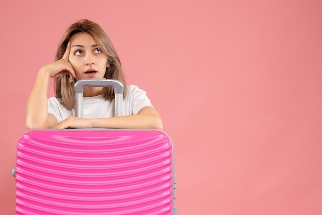 Jeune femme réfléchie, debout derrière une grosse valise