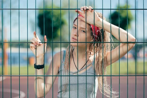 Jeune femme réfléchie portant des vêtements décontractés et s'appuyant sur la clôture à mailles de chaîne après une formation épuisante