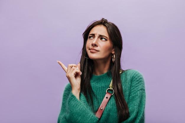 Une jeune femme réfléchie en robe tricotée verte pose sur isolé