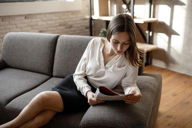 Jeune femme réfléchie s'asseoir sur le canapé en costume de bureau. elle a lu et baissé les yeux. femme assise seule dans la chambre.