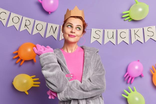 Une jeune femme réfléchie se prépare pour les vacances domestiques porte des vêtements décontractés, des stands avec une expression de rêve organise une soirée à thème pendant des poses de coronavirus contre des ballons multicolores