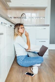 Jeune femme réfléchie avec une tasse de café et un ordinateur portable dans la cuisine moderne et lumineuse à la maison.