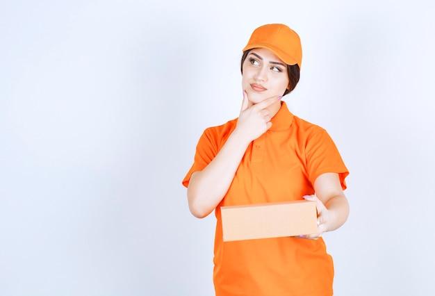 Une jeune femme réfléchie tenant une boîte sur un mur blanc