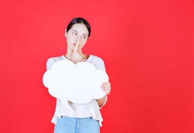 Jeune femme réfléchie tenant une bulle de dialogue avec une forme de nuage