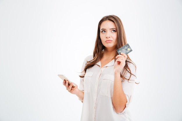 Jeune femme réfléchie tenant une carte de crédit et utilisant un smartphone isolé sur un mur blanc