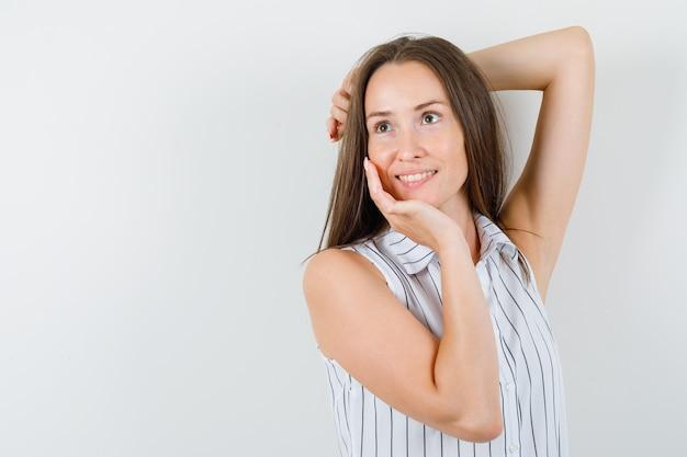 Jeune femme regardant ailleurs tout en pensant en t-shirt et à la jolie. vue de face.