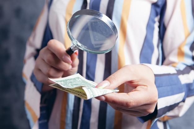 Jeune femme regardant de l'argent avec une loupe