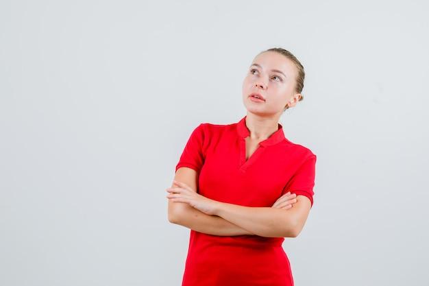 Jeune femme regardant avec les bras croisés en t-shirt rouge et à la pensive