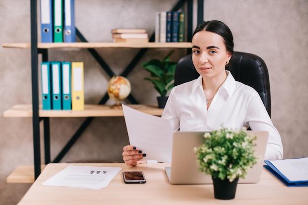 Jeune femme regardant la caméra au bureau