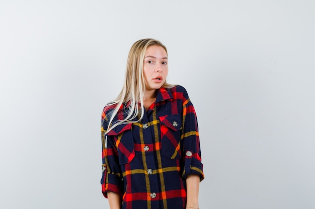 Jeune femme regardant la caméra en chemise à carreaux et à la perplexité, vue de face.