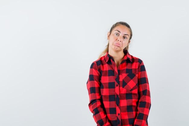 Jeune femme regardant la caméra en chemise décontractée et à la perplexe. vue de face.