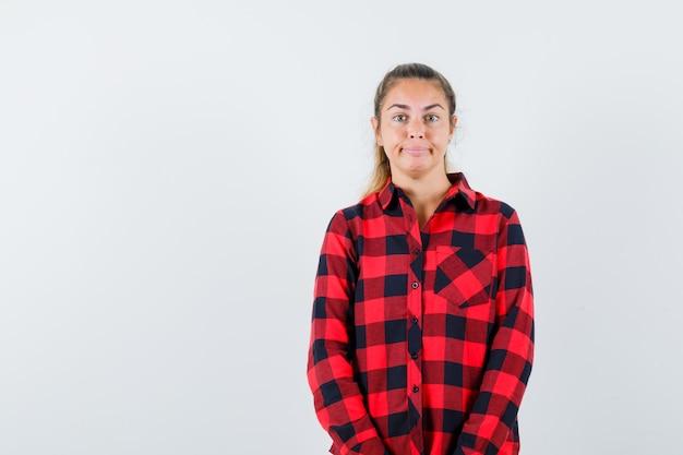 Jeune femme regardant la caméra en chemise décontractée et à la recherche raisonnable. vue de face.