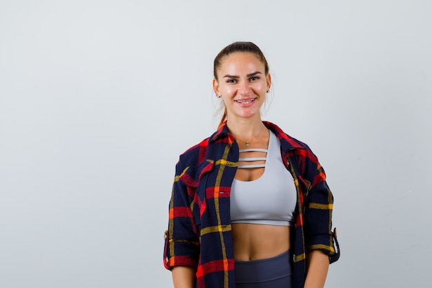 Jeune femme regardant la caméra en haut court, chemise à carreaux, pantalon et l'air heureux, vue de face.