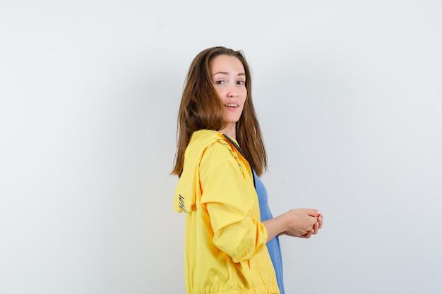 Jeune femme regardant la caméra avec les mains jointes en t-shirt, veste et l'air confiant.