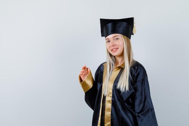 Jeune femme regardant la caméra en robe académique et ayant l'air confiant