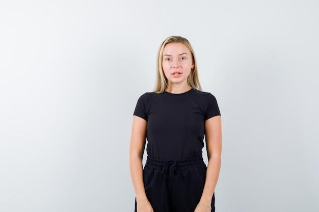Jeune femme regardant la caméra en t-shirt, pantalon et à la jolie vue de face.