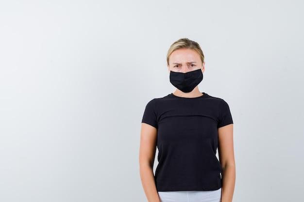 Jeune femme regardant la caméra en t-shirt, pantalon, masque médical et l'air nostalgique