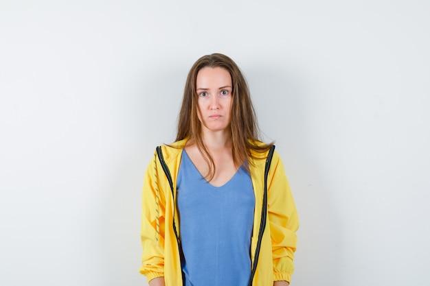 Jeune femme regardant la caméra en t-shirt et semblant sérieuse. vue de face.