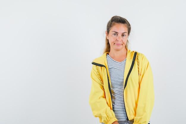 Jeune femme regardant la caméra en t-shirt, veste et à l'insatisfaction. vue de face.