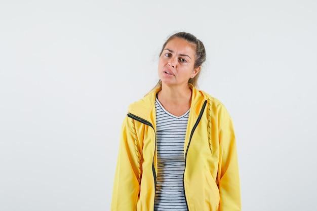 Jeune femme regardant la caméra en t-shirt, veste et à la perplexité. vue de face.