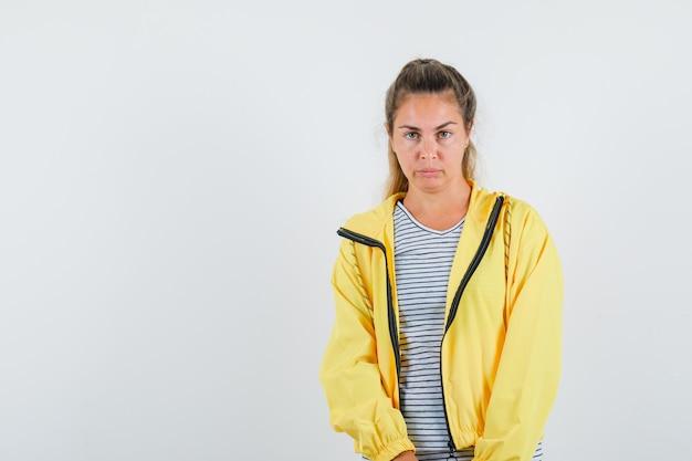 Jeune femme regardant la caméra en t-shirt, veste et regardant pensif, vue de face.