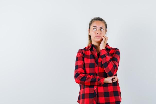 Jeune femme regardant en chemise à carreaux et à la pensif