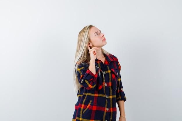 Jeune femme regardant en chemise à carreaux et regardant réfléchie, vue de face.