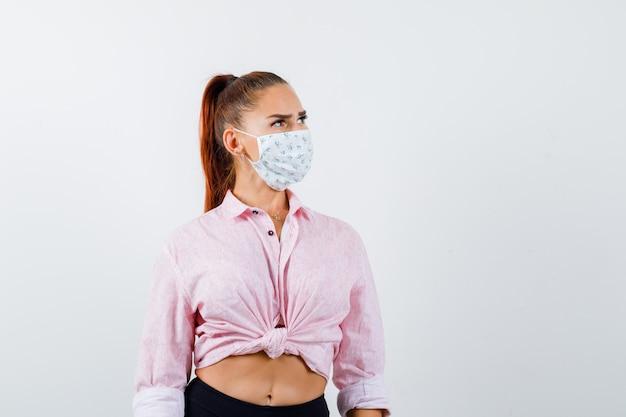 Jeune femme regardant en chemise, masque et à la vue de face, hésitante.