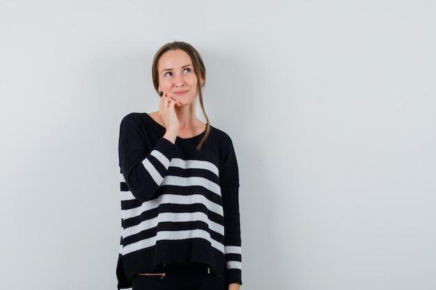 Jeune femme regardant en chemise et à la recherche de rêve