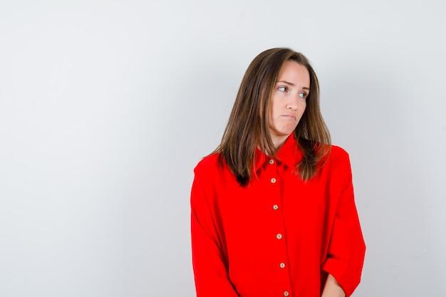 Jeune femme regardant sur le côté en chemisier rouge et semblant lésée, vue de face.