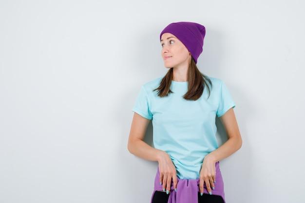Jeune femme regardant de côté avec les mains devant elle en t-shirt, bonnet et l'air concentré, vue de face.