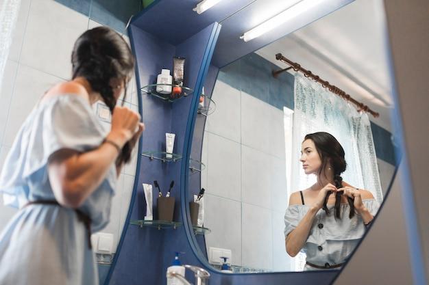 Jeune femme regardant dans le miroir attachant ses cheveux