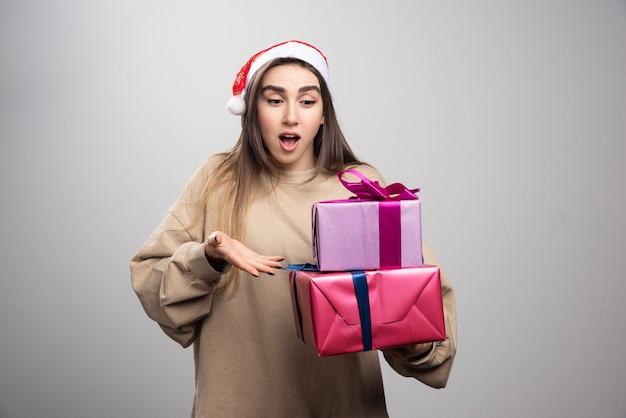 Jeune femme regardant deux boîtes de cadeaux de noël.