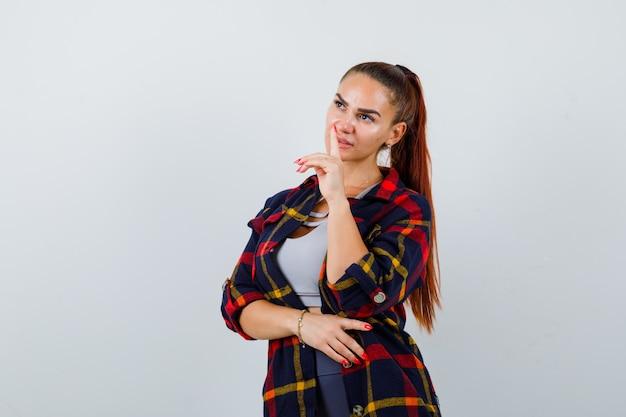 Jeune femme regardant loin en crop top, chemise à carreaux, pantalon et à la réflexion. vue de face.